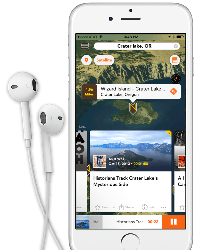 White and sliver iPhone 6 with headphones on the left displays a screen shot of the Nearstory app. On the screen is a 3D map of Crater Lake with focus on Wizard Island. At the top of the screen is a search field that displays Crater Lake, OR. In the middle of teh screen is a Nearstory logo pin and a text cloud with the following: Wizard Island - Crater Lake, Crater Lake, Oregon. 1.96 Miles away. Below Wizard Island at the bottom of the screen is a square story card displaying the playing audio story. On the card is a picture of Wizard Island and Crater Lake, Oregon. Logo for podcast (As It Was) sits in the lower left hand corner. To the right of the podcast logo is the podcast producer title (As It Was). Below the producer title is a publish date of October 15, 2013. to the right of the publish date is a runing time of 1 minute and 58 seconds. Just below the crater lake image in the story card is the title of the podcast episode, 'Historians Track Crater Lakes Mysterious Side. At the bottom of the card is four links, Favorite, Share, Info and an Elipse. Below the audio story card sitting at the bottom of the iPhone screen is a audio player displaying the audio story image to the right with a long strip of white with a gray status bar the audio track srolling through the palyer and the current track time with a large rectangular orange pause button on the right. Behind the iphone is a beautiful picture of Crater Lake National Park. The image fills the entire width of the screen. Snow lightly covers the ground and the sun is bright and dramatic. It looks like it was an early morning or dusk shot. The temperature looks crisp. The water is a deep blue, not a dark blue but not light either. Pine trees can be seen on the left side of the image. In the middle of the shot is Wizard Island looking like a small volcano.